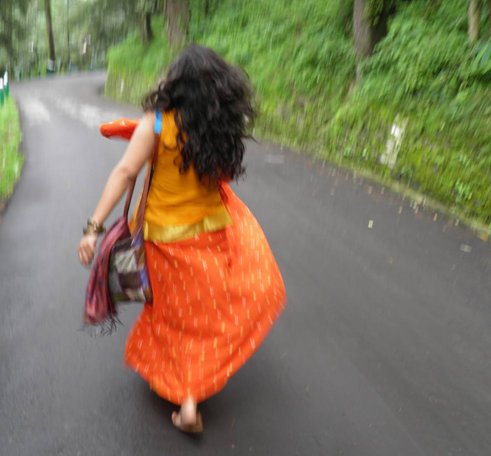 Woman in orange top and skirt walking away from camera.