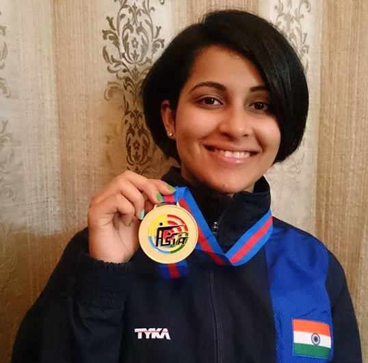 Photo of Heena Sidhu holding up her medal.