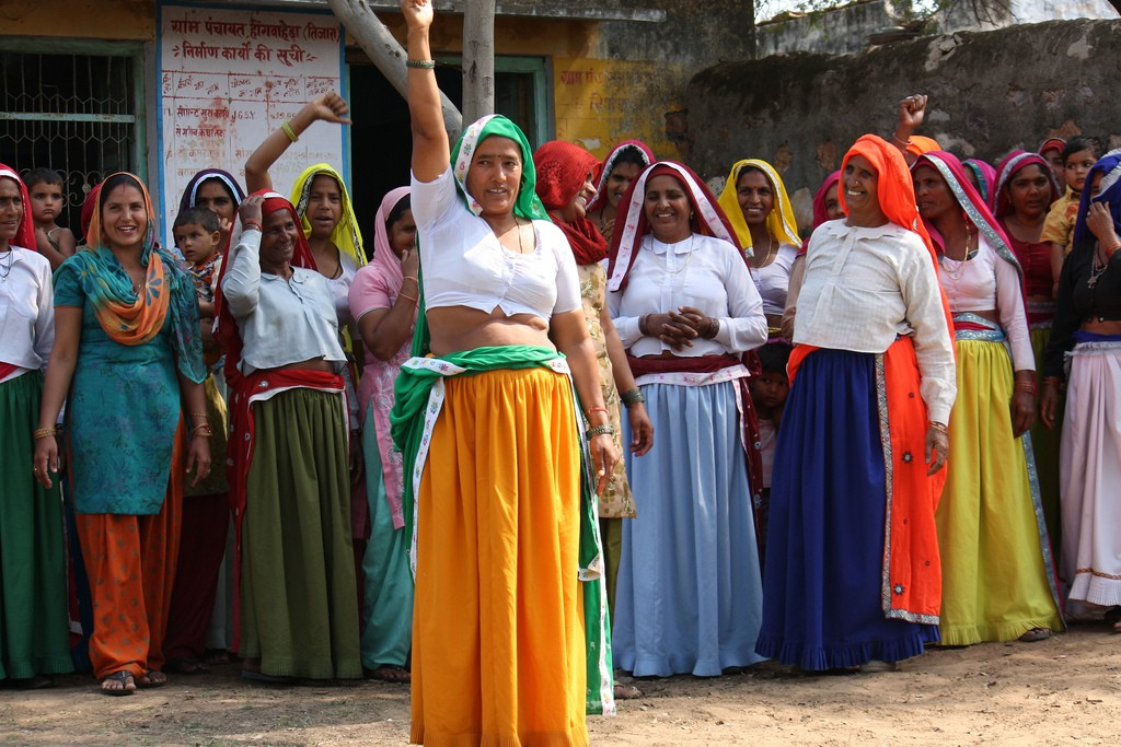 Group of women standing. The one in the foreground with fist raised.