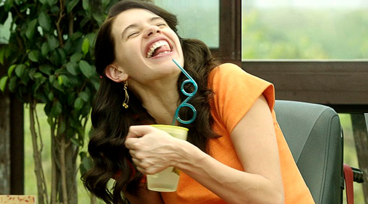 Still from Margarita with a Straw – Kalki Koechlin's character smiles and tries to drink from a straw.