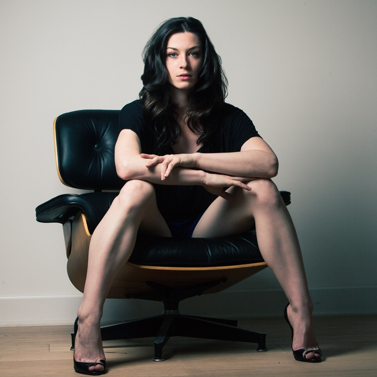 Woman sits on chair, legs spread.
