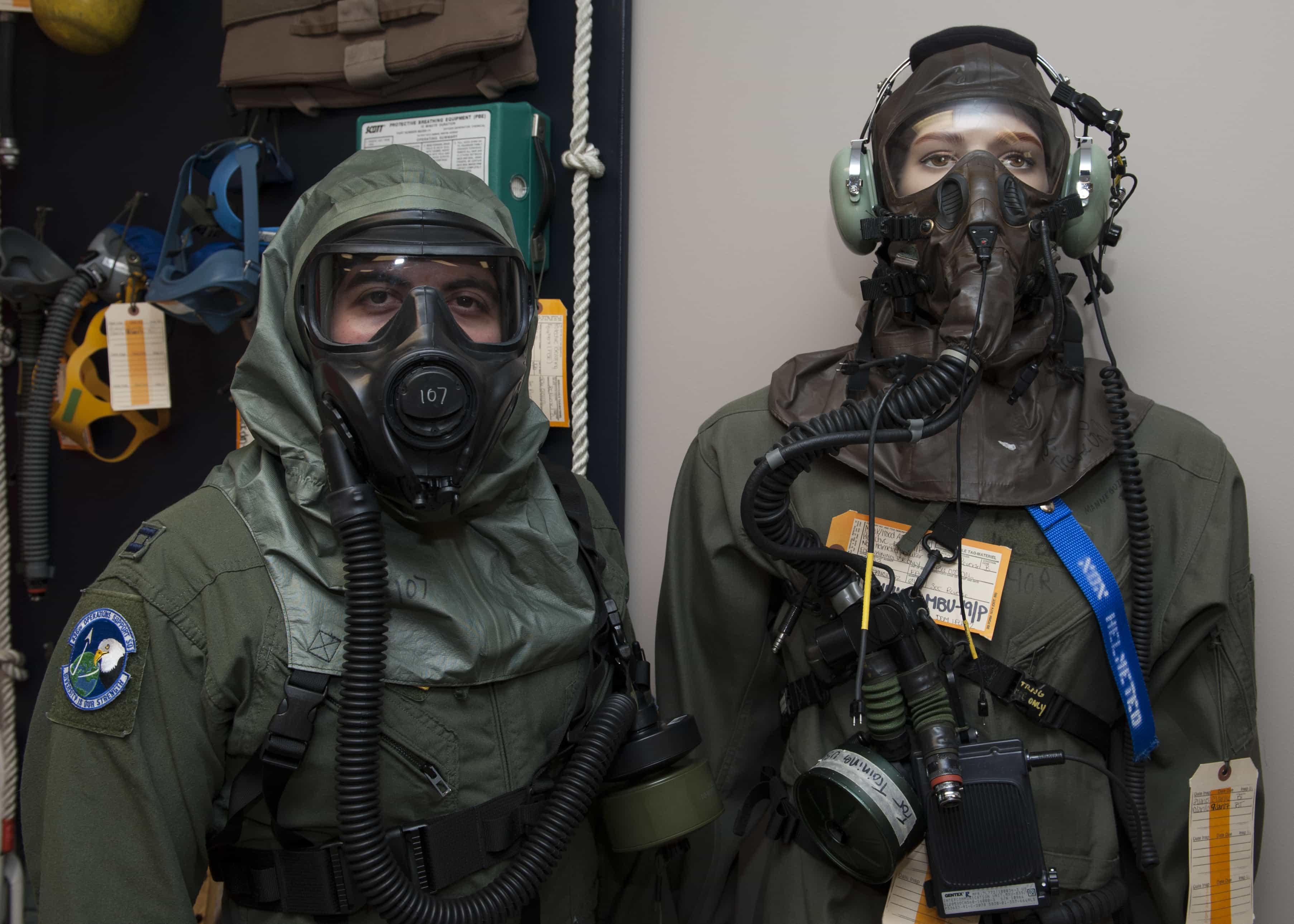 Capt. Edward Silva, 436th Operations Support Squadron Aircrew Flight Equipment commander, poses while wearing the XM69 Aircrew Chemical, Biological, Radiological and Nuclear Defense (CBRN) system while standing next to a mannequin wearing the legacy U.S. Air Force Aircrew Eye Respiratory Protection (AERP) system March 2, 2016, inside the Aircrew Flight Equipment facility on Dover Air Force Base, Del. These masks are worn by aircrew members in the event they are exposed to a chemical, biological, radiological or nuclear environment. (U.S. Air Force photo/Senior Airman Zachary Cacicia)
